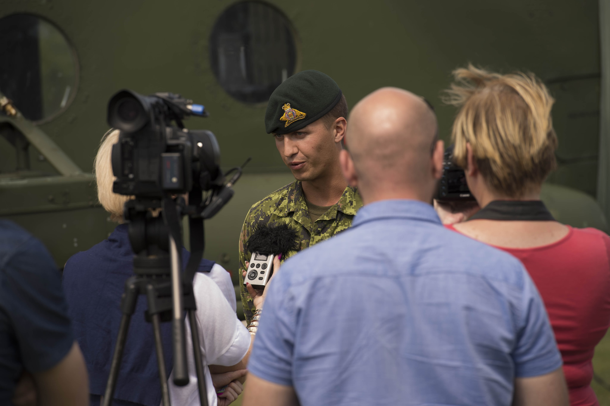 A soldier speaks to media members in front of a camera
