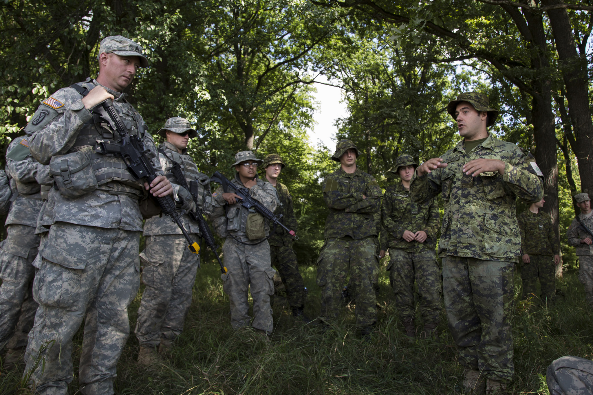 Corporal Sonny Gauthier (right), a medical technician of 5 Field Ambulance deployed as part of the Operation REASSURANCE Land Task Force (LTF), explains to LTF colleagues and American soldiers of the 116th Cavalry Brigade Combat Team how to triage casualties during Exercise SABER GUARDIAN, a multinational exercise comprising 10 countries, in Cincu, Romania on August 3, 2016. The LTF is deployed to Central and Eastern Europe to support NATO assurance and deterrence measures, and improve interoperability with allies. (Photo: Corporal Guillaume Gagnon, Liaison Officer Driver, Operation REASSURANCE Land Task Force)