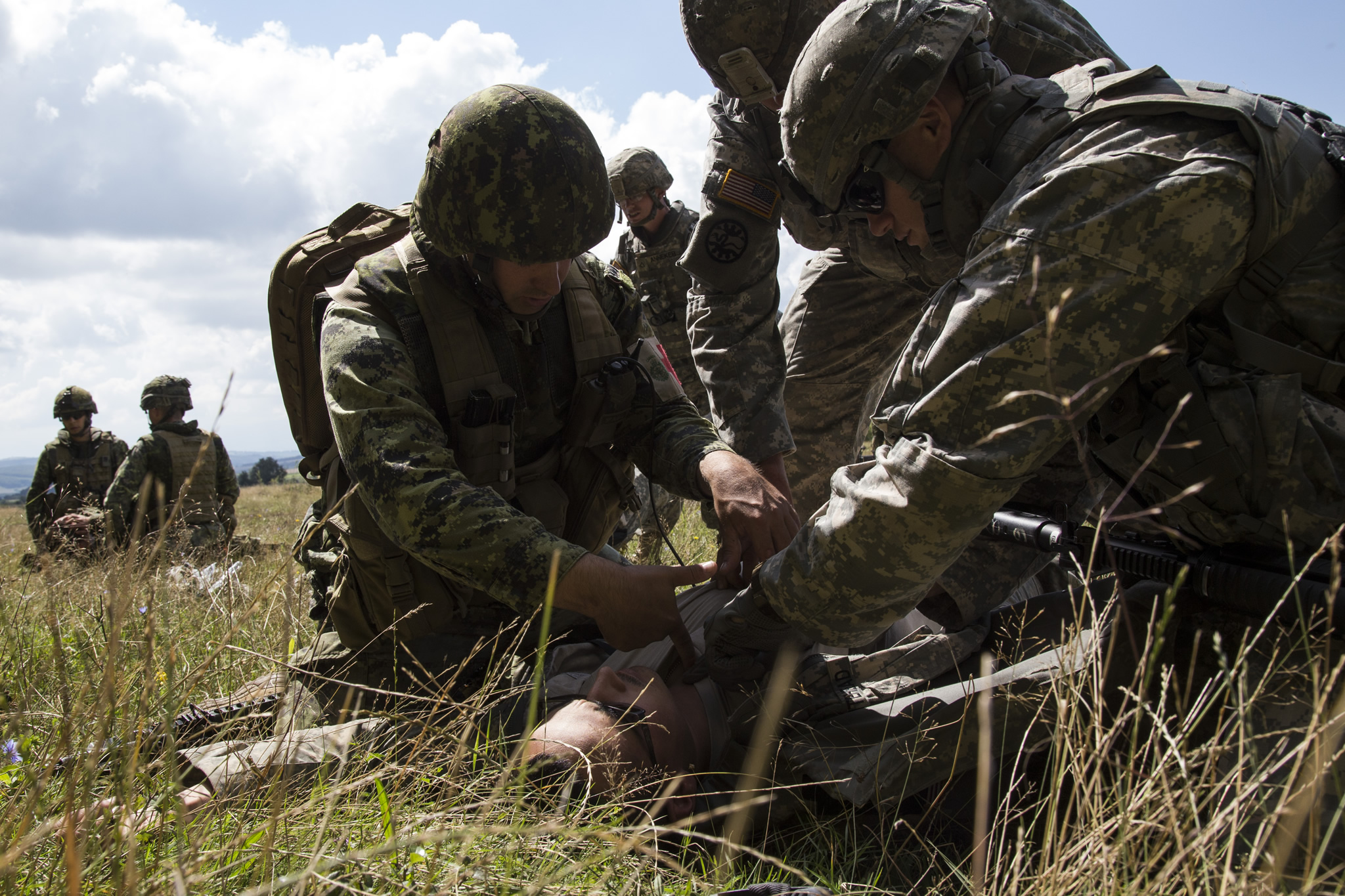 Corporal Sonny Gauthier (left), a medical technician of 5 Field Ambulance deployed as part of the Operation REASSURANCE Land Task Force (LTF), provides first aid advice to American soldiers of the 116th Cavalry Brigade Combat Team during Exercise SABER GUARDIAN, a multinational exercise comprising 10 countries, in Cincu, Romania on August 3, 2016. Canadian soldiers are deployed to Central and Eastern Europe as part of the LTF to support NATO assurance and deterrence measures, and improve interoperability with allies. (Photo: Corporal Guillaume Gagnon, Liaison Officer Driver, Operation REASSURANCE Land Task Force)