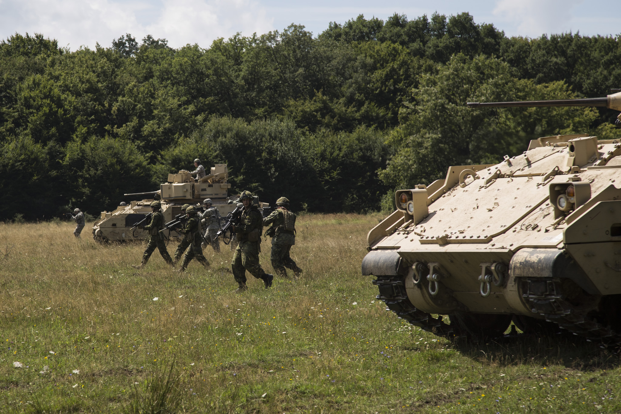 Soldiers walk in a field alongside two tanks.
