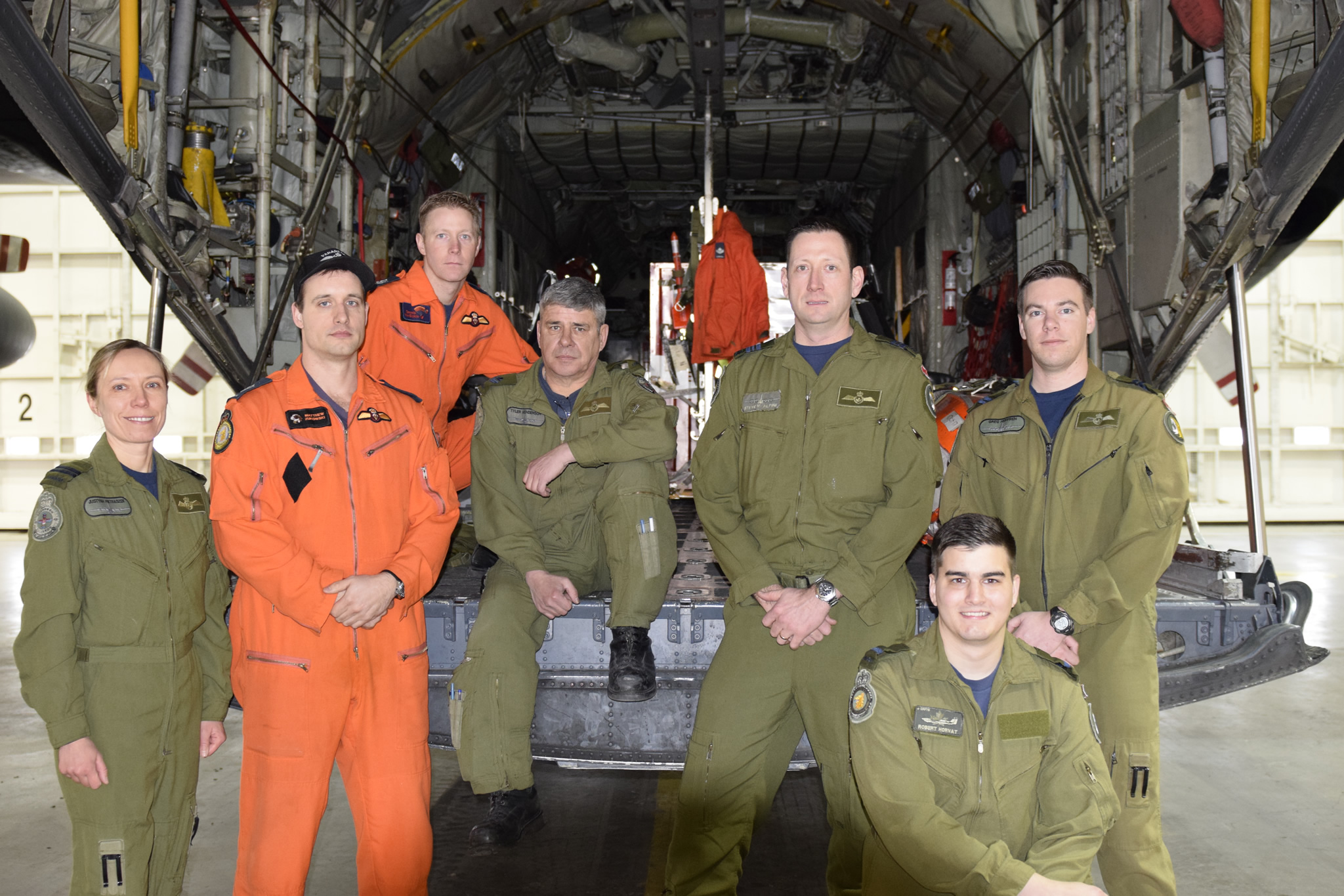 Baker Lake SAR crewmembers (L to R) Captain Justyna Pietraszek (ACSO), Master Corporal Matthew Zukowski (SAR Tech), Sergeant Dennis Van Sickle (SAR Tech), Master Corporal Tyler Henderson (Loadmaster), Major Steve McAlpine (Aircraft Commander), Second Lieutenant Robert Horvat (SAR Spotter), and Captain Greg Heffren (First Officer) pose on the rear ramp of a CC-130H Hercules at 424 Transport and Rescue Squadron at 8 Wing Trenton, 3 February, 2017. Missing from photo: Master Corporal Jason Tibbo, Flight Engineer.  (Photo credit: 8 Wing Public Affairs ©2017 DND-MDN Canada)
