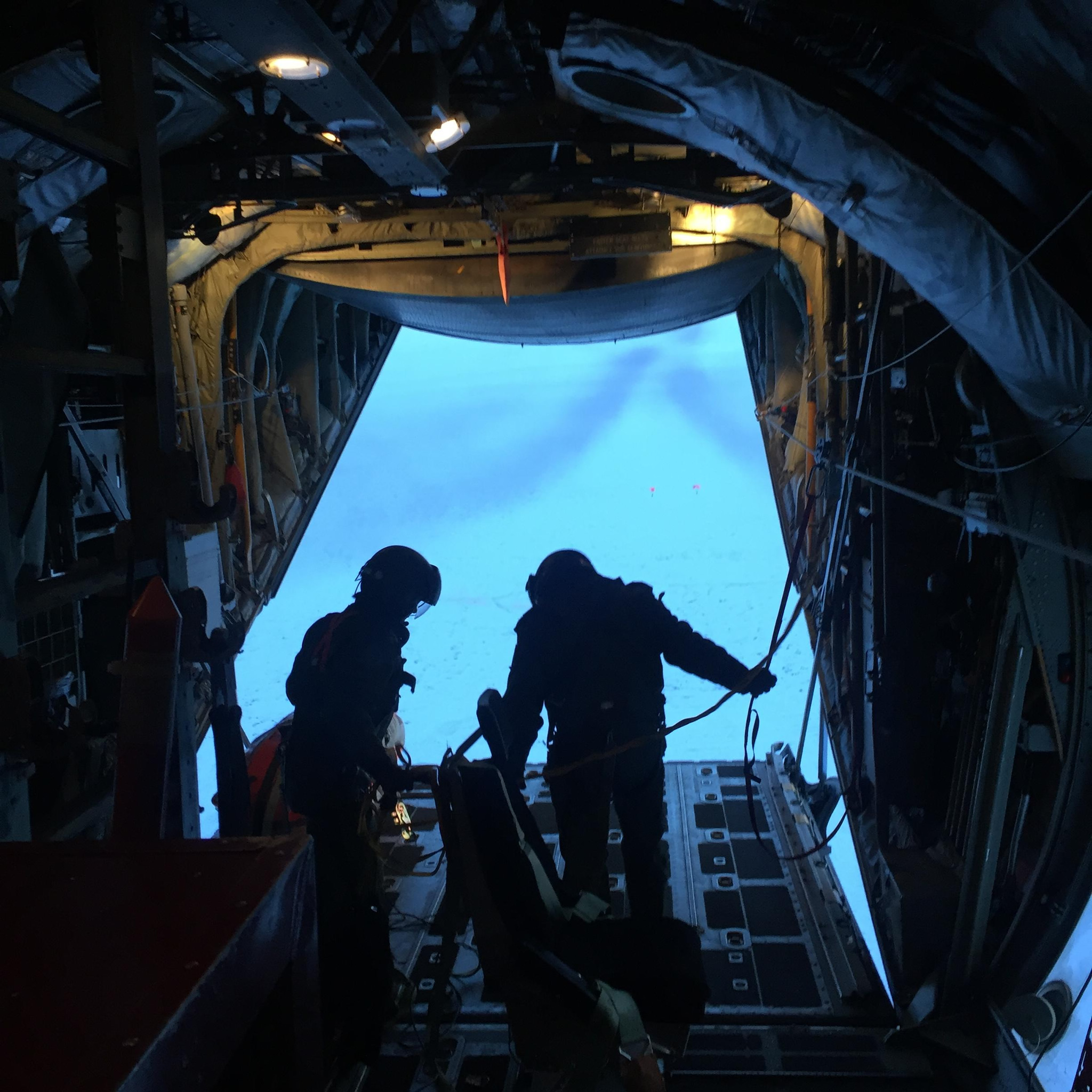 Two soldiers hold onto to lines and deployment bags on board an aircraft after two other soldiers exited the aircraft.