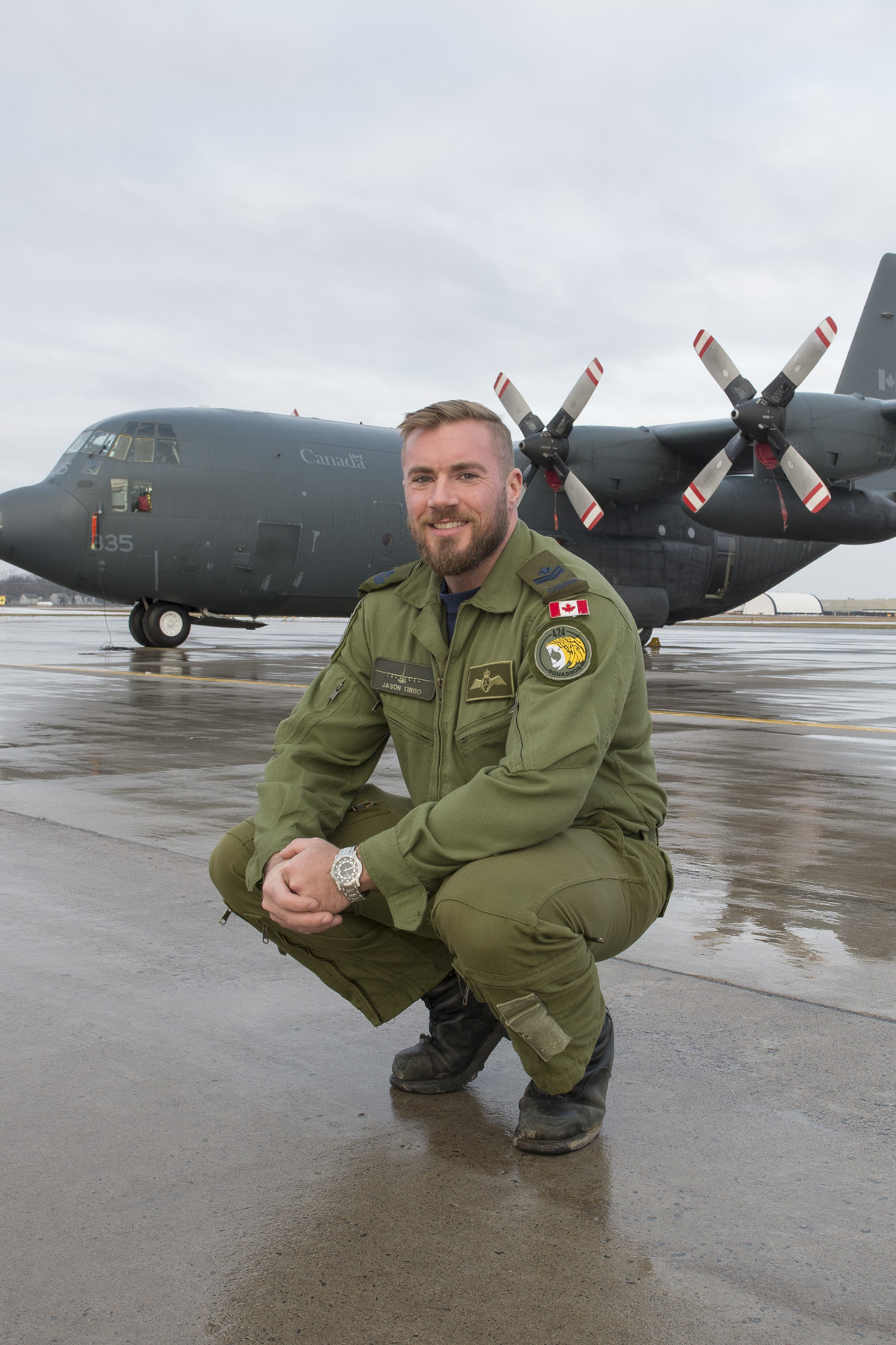 Master Corporal Jason Tibbo, Flight Engineer for the Baker Lake SAR mission, poses in front of a CC-130H Hercules at 8 Wing Trenton, 19 January, 2017. (Photo credit: Corporal Audrey Solomon, 8 Wing Imaging ©2017 DND-MDN Canada)