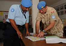 Pyla, Cyprus. 24 November 2008 – Captain Michael Solonynko (right), Operation and Information Analyst Officer for the UN HQ in Cyprus, discusses patrol routes to prevent overlapping patrols with UN Civilian Police Officer Nasir Ahmed from India, the Detachment Commander of Pyla Station. (Photo by MCpl Robert Bottrill, Canadian Forces Combat Camera)