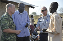 Juba, South Sudan, 7 December 2012 – Major Jan-Peter Hoekstra and Sergeant Robert Hagarty of the Ottawa police service speak with two men about the drilling of a well for a small school in Juba. (photo by: Sgt Norm McLean, Canadian Forces Combat Camera).