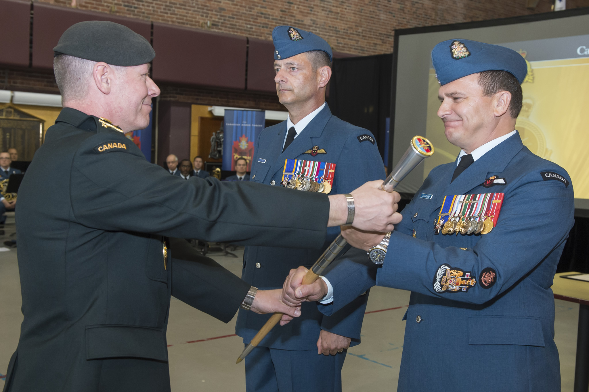 Ottawa, Canada. 2 June 2015 –  Lieutenant-General (LGen) Jonathan Vance (left), Commander of Canadian Joint Operations Command (CJOC), passes the Chief Warrant Officer (CWO) pace stick from CWO Gerard Poitras (Centre), Outgoing Command CWO, to CWO Gaudreault (right), Incoming Command CWO, during the CJOC Change of Command and Change of Appointment Ceremony. (Photo credit: Corporal Lisa Fenton. Canadian Forces Support Unit (Ottawa) Imaging Services ©2015 DND-MDN, Canada)