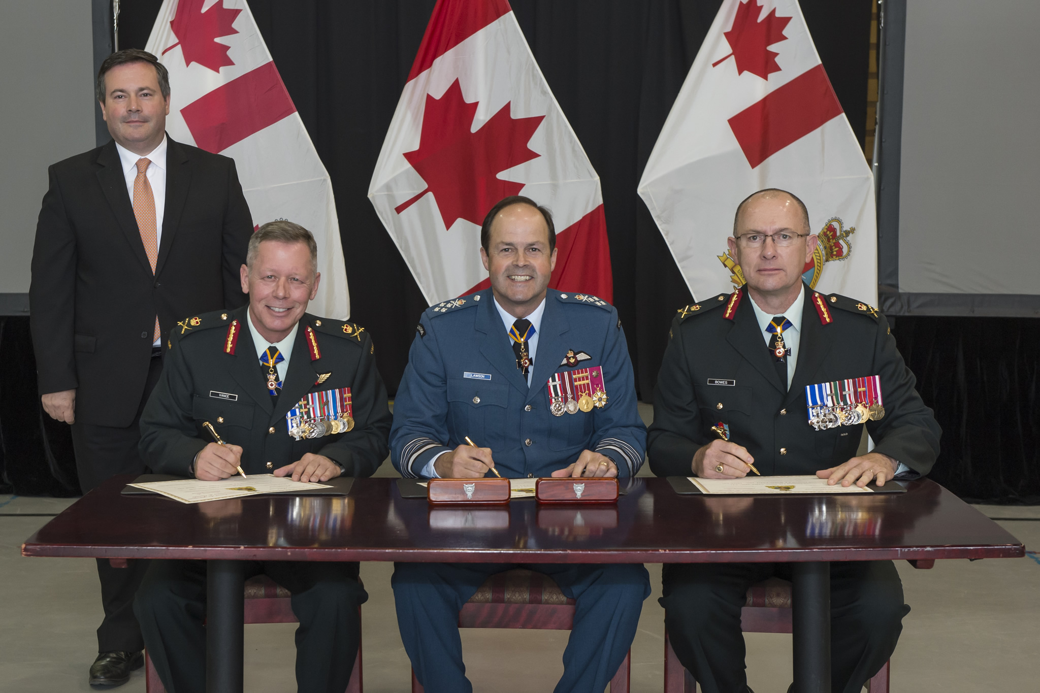Three generals sign documents at a table while a man stands behind them