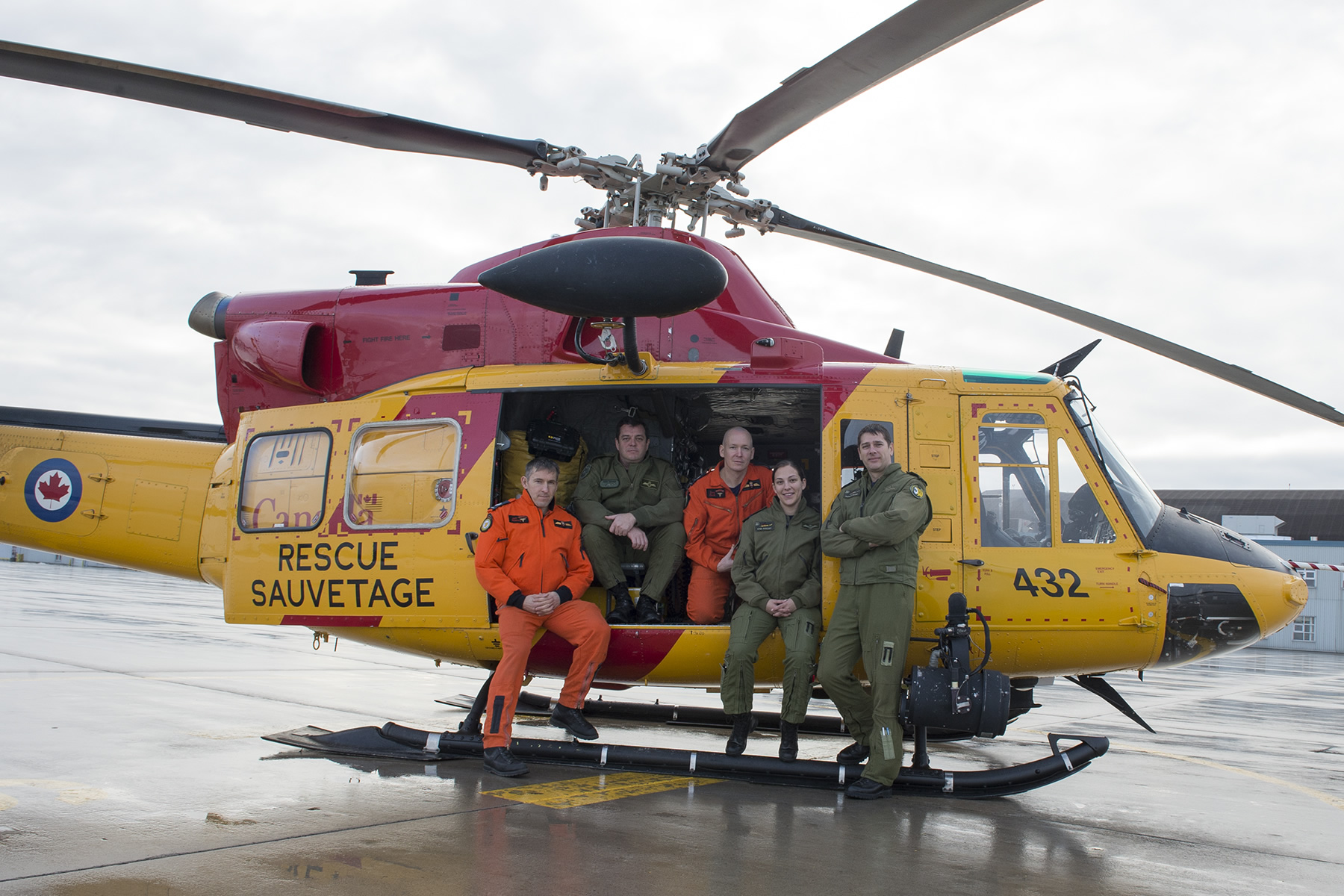 Five people stand in front of or sit in a yellow helicopter.