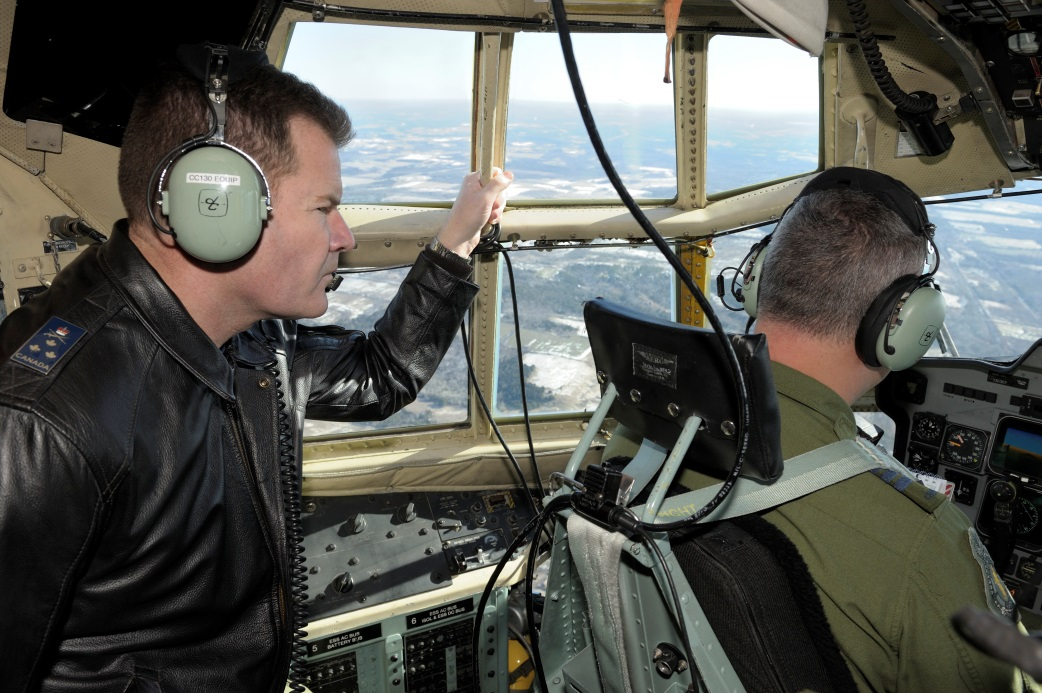 Two men in the cockpit of an aircraft.