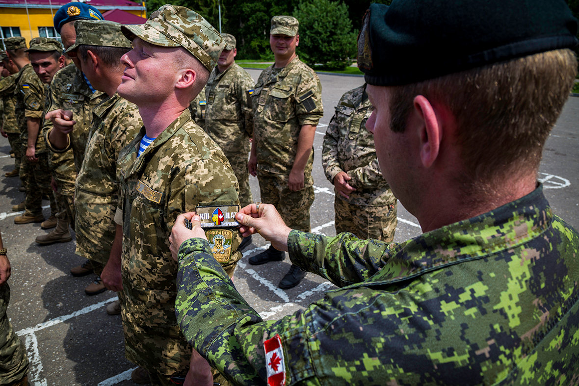 A soldier receives a badge from another soldier.