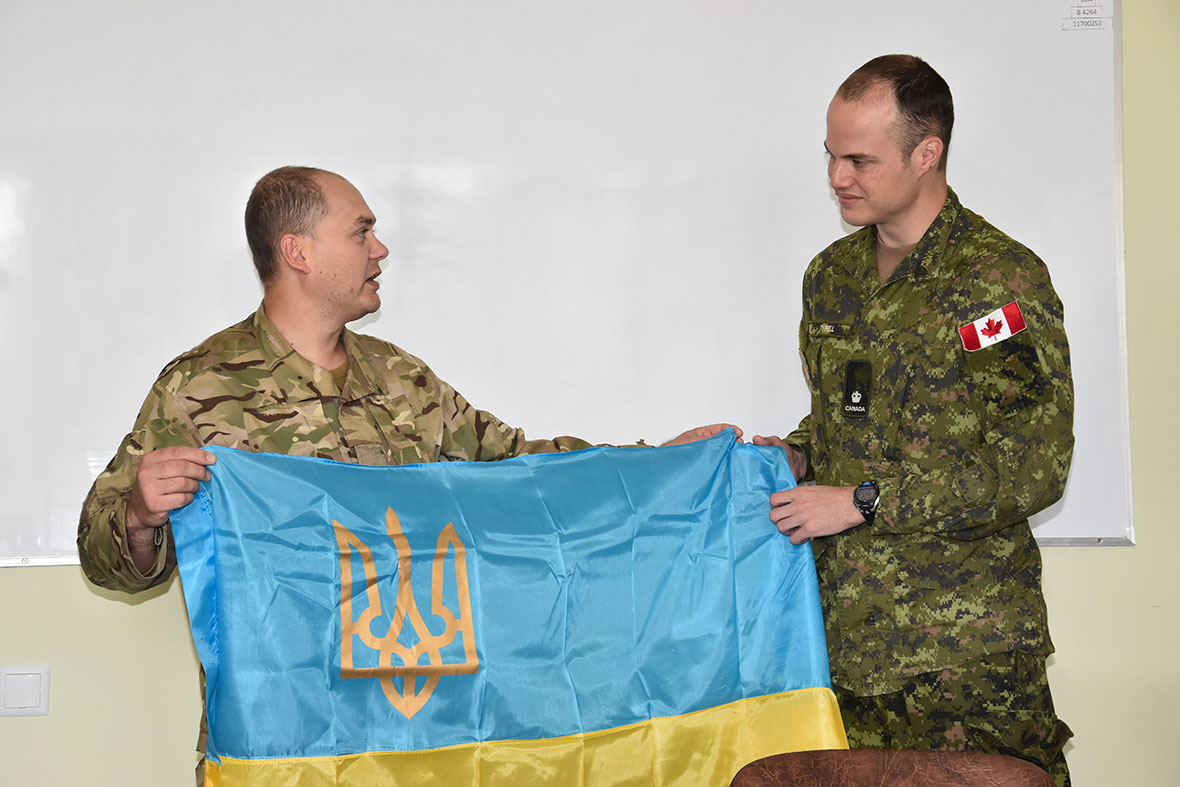 A soldier in a classroom presents another soldier with the Ukrainian flag as a token of appreciation.