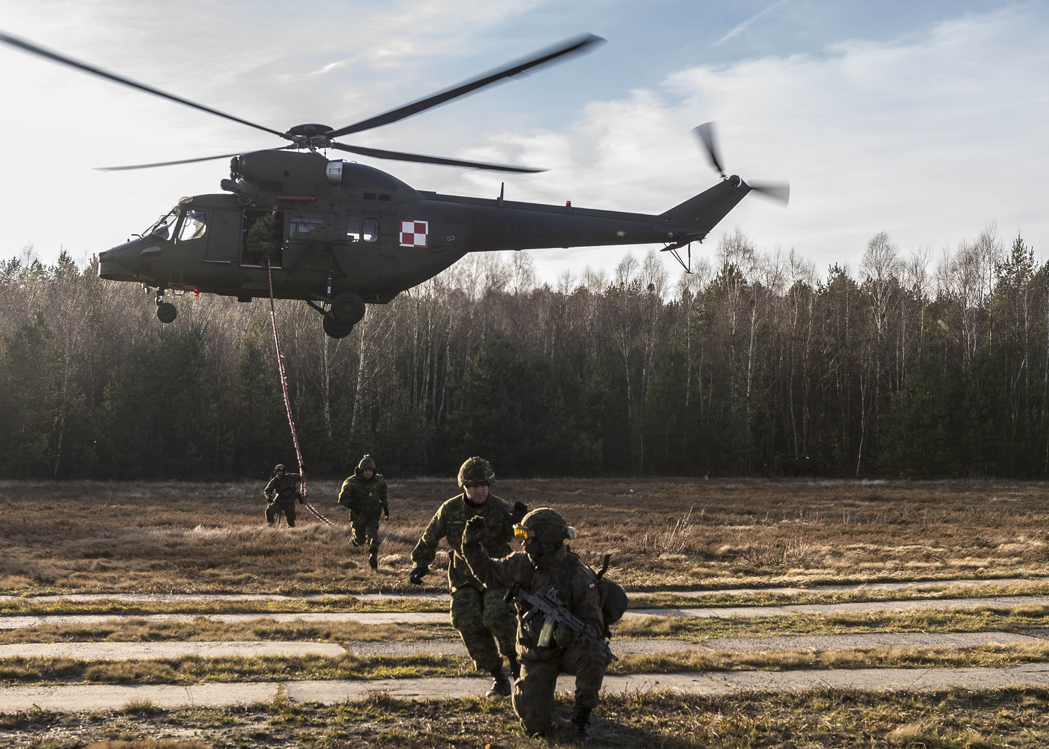 Canadian and Polish Armed Forces members decend from a helicopter on a rope during a fast rope exercise at Nowa Dęba Training Center in Nowa Dęba, Poland on December 4, 2015 during Operation REASSURANCE.