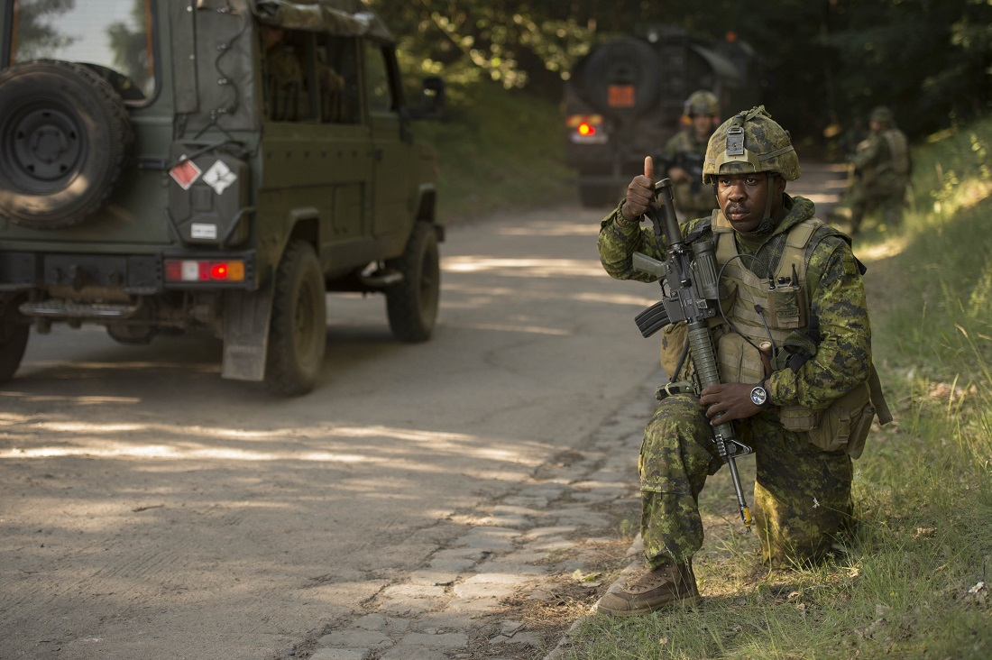 June 7 2016. Wȩdrzyn, Poland. Private Josaphat Nicolas-Marchal, a soldier of the 1st Battalion Royal 22e Régiment deployed with the Operation REASSURANCE Land Task Force (LTF), gives a thumbs-up to Polish vehicles to let them know that it is safe to pass during Exercise ANAKONDA-16, a multinational  military exercise involving 23 nations, in Wȩdrzyn, Poland on June 7, 2016. The Canadian soldiers are deployed as part of the LTF to support NATO assurance measures in Central and Eastern Europe. (Photo: Master Corporal Andrew Davis, Operation REASSURANCE Land Task Force Imagery Technician)