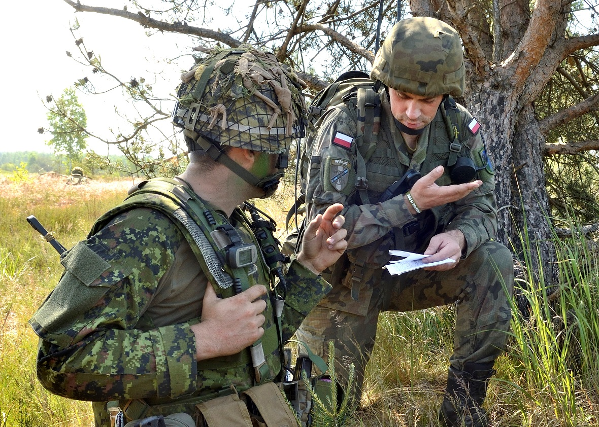 Captain Kyle Chamhart from C-Company, 3rd Battalion Princess Patricia's Canadian Light Infantry coordinates exercise details with a member of the Polish Army during Exercise SABRE STRIKE in Poland on June 15, 2017, as part of Operation REASSURANCE. Photo by: MCpl Brandon O'Connell, Image Tech, 3rd Cdn   Div PA