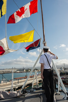 July 01, 2016. Ordinary Seaman Jesse Godard, a Naval Communicator on Her Majesty's Canadian Ship (HMCS) Calgary, salutes the Canadian flag as it is raised on Canada Day during RIMPAC 16 at Joint Base Pearl Harbour-Hickam, Hawaii on July 01, 2016. (Photo: MCpl Chris Ward, MARPAC Imaging Services)