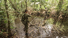 Belize. 20 June 2015 - Two participants of jungle training from the Canadian Armed Forces and Jamaica Defence Force cross a river while trying to stay dry during phase II of Exercise TRADEWINDS 15. (Photo: Sgt Yannick Bédard, Canadian Forces Combat Camera)