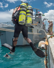Un plongeur des Forces armées canadiennes saute de la jetée au cours de l'exercice TRADEWINDS 16, à Montego Bay, en Jamaïque, le 20 juin 2016. Photo : Capitaine Christopher Daniel, Caméra de combat des Forces canadiennes. (Photo: cplc McMillan, Caméra de combat)