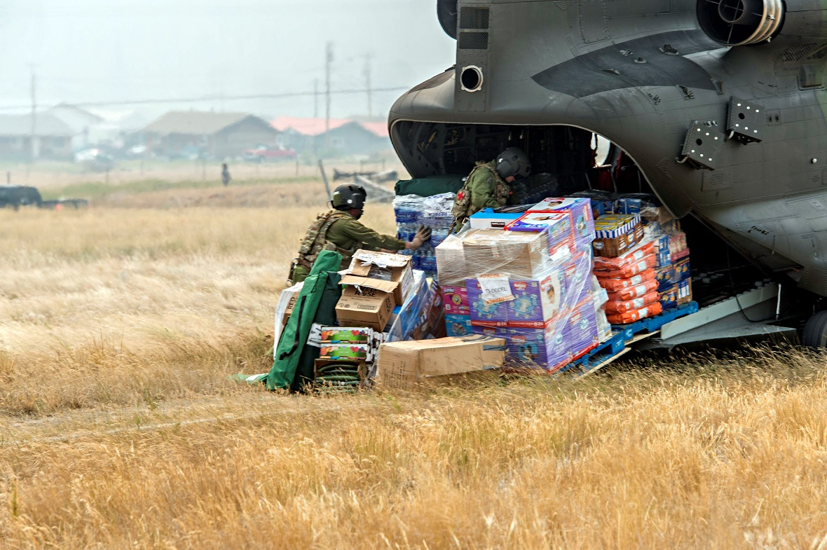 Flight Engineers unload supplies from a CH-147 Chinook helicopter in a cut off community during Operation LENTUS 17-04 in British Columbia on 18 July 2017. Photo: MCpl Gabrielle DesRochers, Canadian Forces Combat Camera