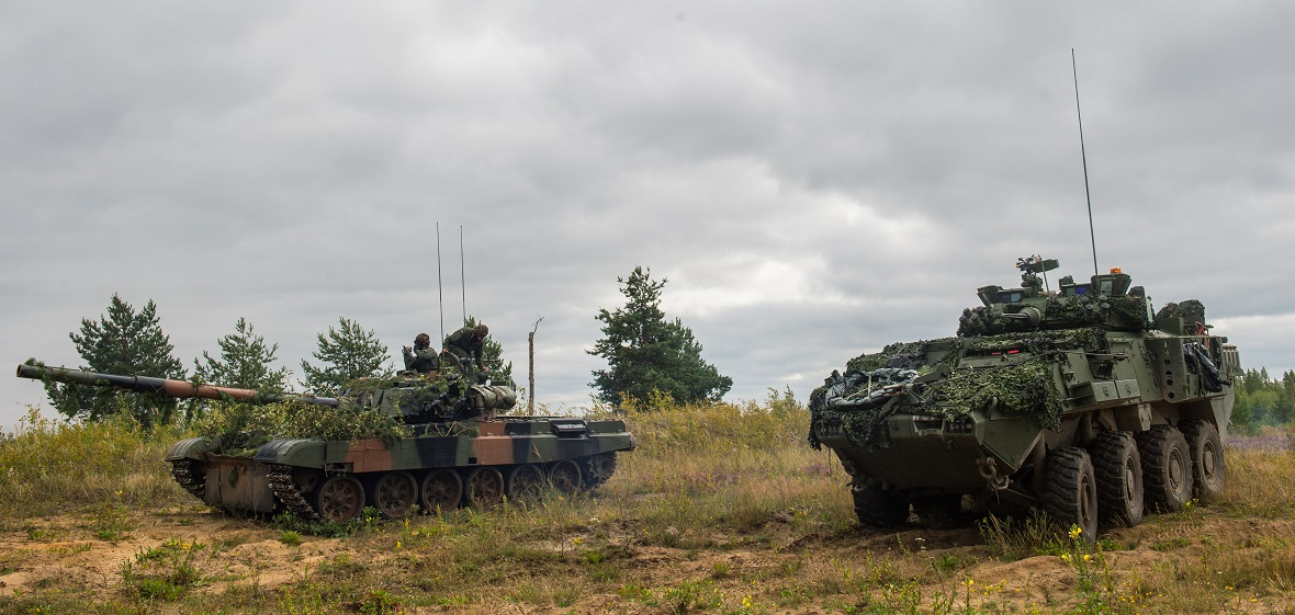 A Canadian light armoured vehicle (LAV-6) and Polish tank (PT-91) with NATO's enhanced Forward Presence Battlegroup Latvia provide mutual support on August 24, 2017, during the Certification Exercise being held at Camp Adazi, Latvia. Photo: Cpl Jordan Lobb, Canadian Forces Combat Camera