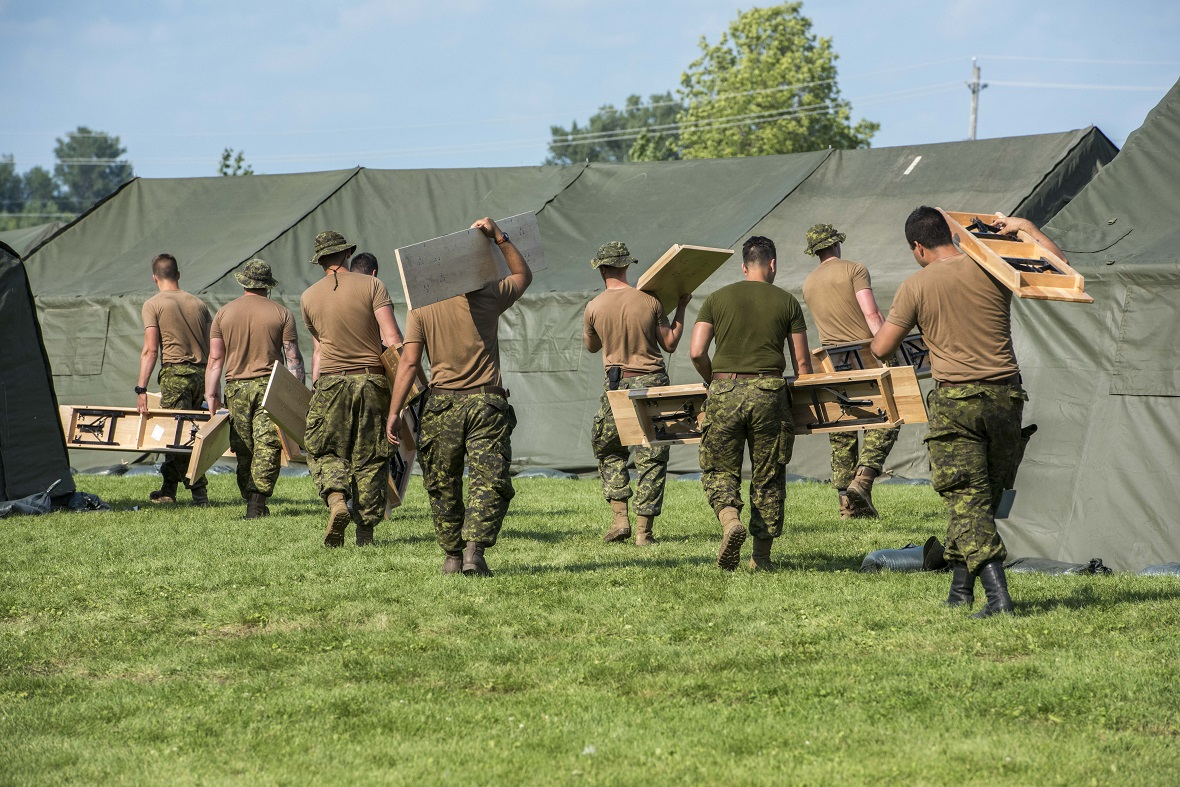 Royal Canadian Dragoons carry tables to install them in the tent city they constructed at the Nav Canada Center in Cornwall, Ontario during Operation ELEMENT, August 18, 2017. Photo: Cpl Veldman, Garrison Imaging Petawawa