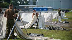 Soldiers from Joint Task Force (East) build a temporary camp to accommodate asylum seekers near the Saint-Bernard-de-Lacolle border crossing in Quebec during Operation ELEMENT, August 9, 2017. Photo: Corporal Myki Poirier-Joyal, St-Jean/Montreal Imagery Section