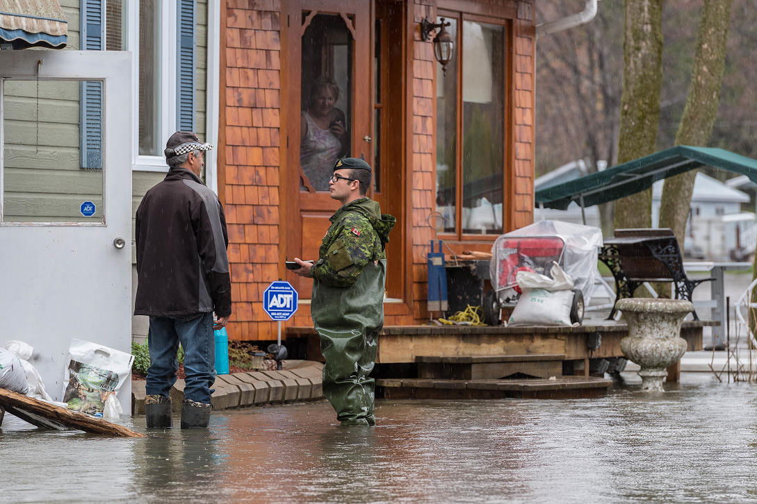 Bombadier Keven Guillette from 5e Régiment d'artillerie légère du Canada talks to residents affected by flooding while assessing the situation of a community in Bécancour, Quebec during Operation LENTUS on May 7, 2017.  (Photo: Cpl Nathan Moulton, Imagery Valcartier)