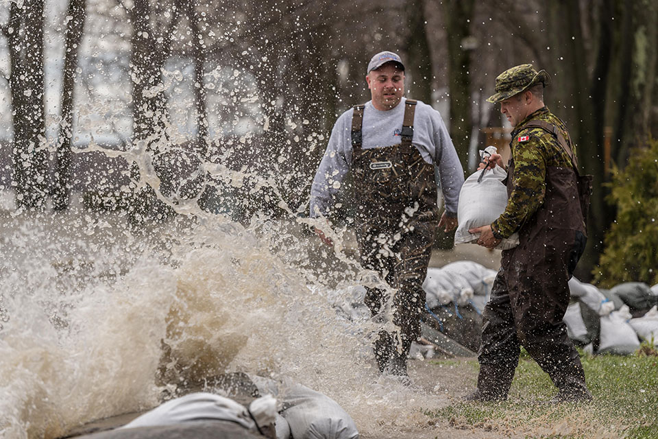 Yamachiche, Quebec. May 7, 2017 – Bombadier Arsenault from 5e Régiment d'artillerie légère du Canada stacks sandbags as waves crash at a residence affected by flooding during Operation LENTUS 17. (Photo by: Cpl Nathan Moulton, Imagery Valcartier)