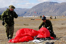 York Sound, Nunavut. 26 August 2014 - Master Corporal Mark Smith a parachute rigger of Canadian Army Advance Warfare Centre, packs his parachute after landing into York Sound, NU during Operation NANOOK 2014. Captain Angelo Manzara (left), the team leader, ensures that he landed successfully without injury. (Photo by MCpl Johanie Maheu, 14 AMS Wing Imaging, 14 Wing Greenwood, NS)