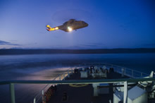Koojesse Inlet, Nunavut. 23 August 2014 - CH-129 Cormorant and HMCS SHAWINIGAN conducting a hoistex at night while at anchor in Koojesse Inlet during Operation NANOOK 2014. (Photo by Lt (N) Davidson-Arnott)
