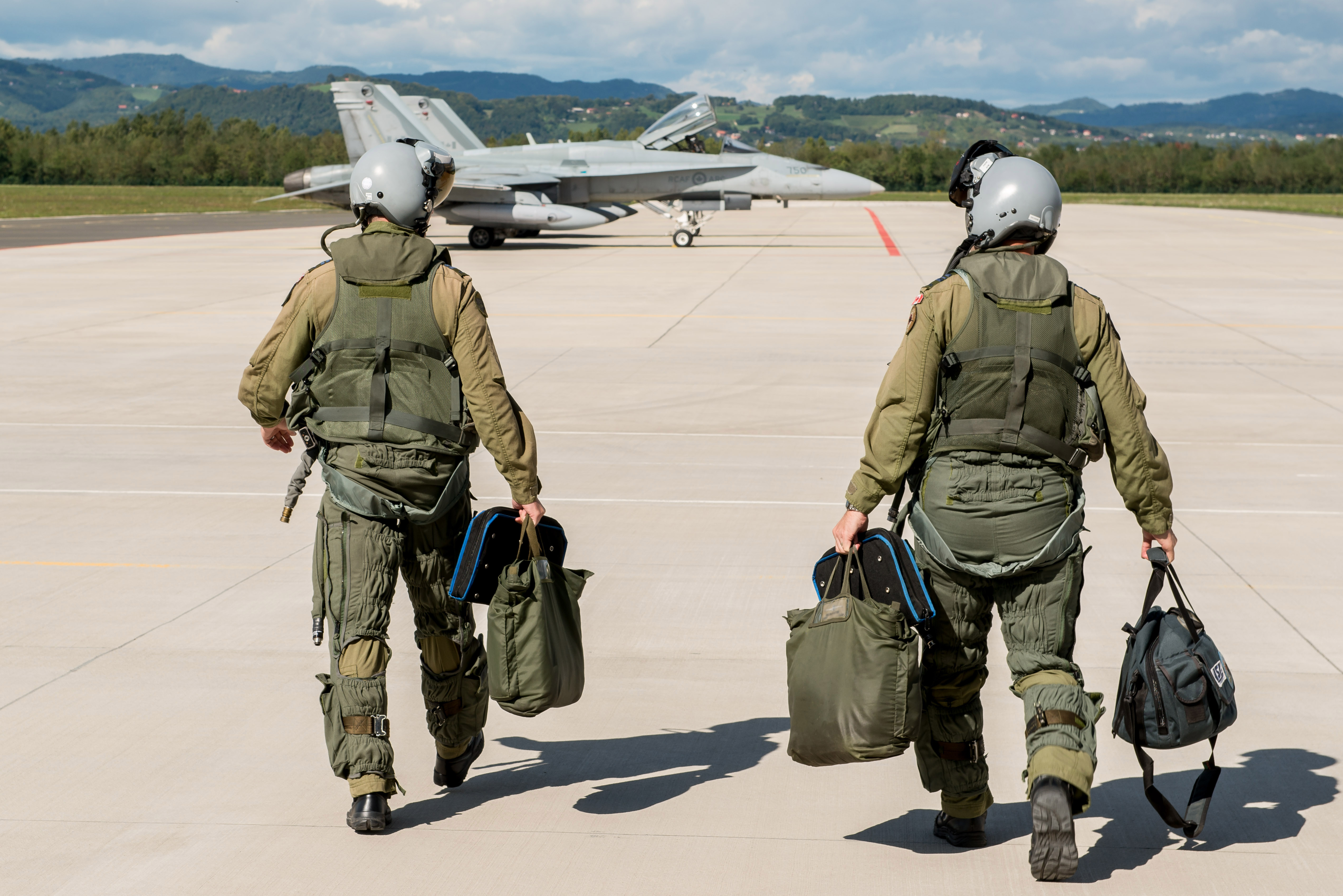Canadian Armed Forces pilots walk towards the CF-188 Hornet aircraft on the tarmac at Cerklje Air Force Base, Slovenia on 21 September 2017 during a bilateral defence visit as part of an outreach activity for Operation REASSURANCE. Image by: Sergeant Daren Kraus